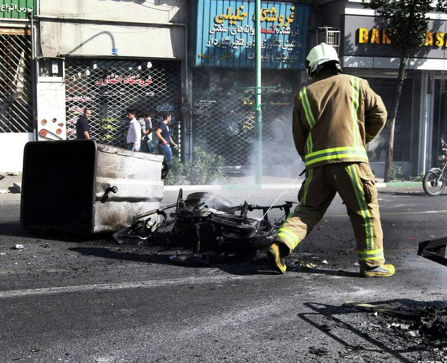 A firefighter extinguishes a motorcycle set ablaze Wednesday in Tehran in this photo that was taken by an onlooker and obtained by the Associated Press. Photo: Anonymous / AP