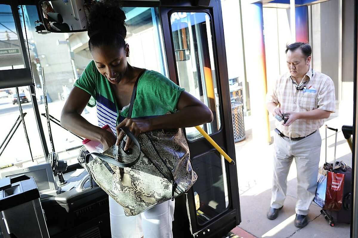 Kerri Spragan, who is returning to LA, has to dig in her purse to find correct change in order to ride the AirBart bus at the Coliseum Bart station in Oakland, CA Wednesday October 3rd, 2012.