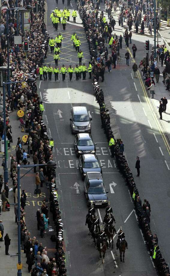 Crowds line the streets as the coffin of Greater Manchester Police constable Nicola Hughes is driven to Manchester Cathedral for her funeral service on October 3, 2012 in Manchester, England. Police Constables Nicola Hughes, 23, and her police colleague Fiona Bone, 32, were killed as they responded to what they thought was a routine burglary call in Mottram, Greater Manchester and were murdered in a gun and grenade attack. The funeral of Fiona Bone also takes place at the cathedral tomorrow. Local man Dale Cregan, 29, appeared before Manchester Magistrates last week accused of four murders, including those of PC Nicola Hughes and PC Fiona Bone on September 18. Photo: WPA Pool, Getty Images / 2012 Getty Images