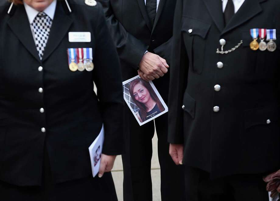 A mourner carries an order of service as the coffin of police Constable Nicola Hughes is carried out of  Manchester Cathedral after her funeral service on October 3, 2012 in Manchester, England. Photo: CHRISTOPHER FURLONG, AFP/Getty Images / 2012 Getty Images