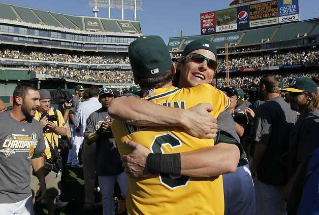 Oakland's Josh Reddick, (right) hugs team manager Bob Melvin, as the Oakland Athletics beat the Texas Rangers 12-5 in the last game of the season to clinch the American League West division in Oakland, Calif., on Wednesday October 3, 2012. Photo: Michael Macor, The Chronicle