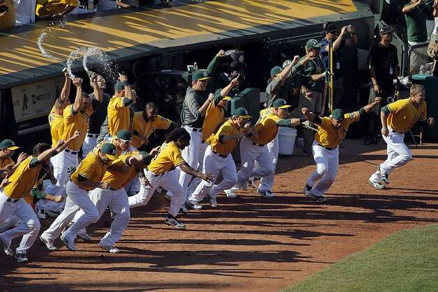 The A's rush from the dugout to mob pitcher Grant Balfour on the mound after the final out of the game defeating the Texas Rangers. The Oakland Athletics won the American League West division after they defeated the Texas Rangers at O.co Coliseum in Oakland, Calif., on Wednesday, October 3, 2012. Photo: Carlos Avila Gonzalez, The Chronicle