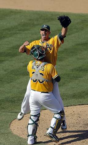 Catcher Derek Norris picks up Grant Balfour after the final out as the A's defeated the Texas Rangers. The Oakland Athletics won the American League West division after they defeated the Texas Rangers at O.co Coliseum in Oakland, Calif., on Wednesday, October 3, 2012. Photo: Carlos Avila Gonzalez, The Chronicle