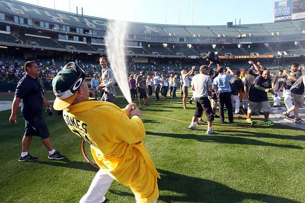 Oakland Athletics Jonny Gomes turns a fire hose on his teammates after they celebrated their 12-5 championship win over the Texas Rangers with a team portrait Wednesday October 3, 2012 in Oakland California Photo: Lance Iversen, The Chronicle