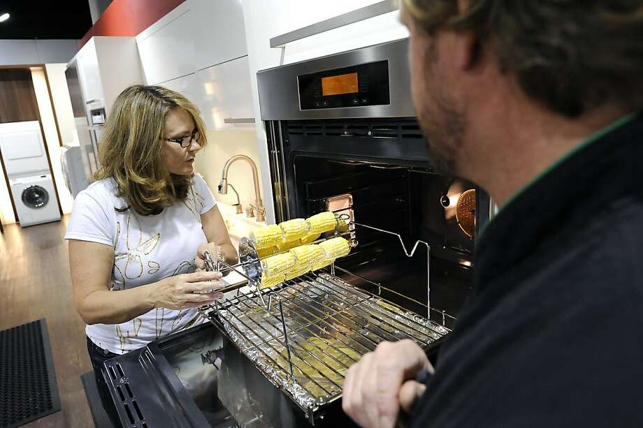Meredith Stout of Oakland prepares to put corn on the cob inside the 30-inch wall oven during a demonstration for shoppers by appliance maker Miele. Photo: Michael Short, Special To The Chronicle