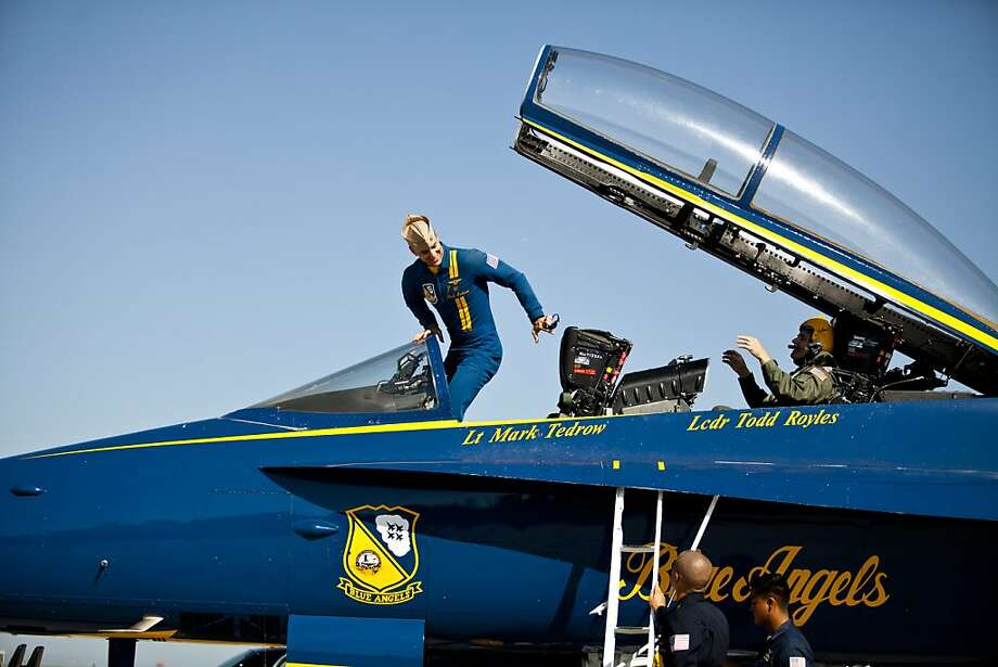 Navy Blue Angel Lt. Mark Tedrow, center, exits the cockpit of an F-18 Hornet on the tarmac at SFO after giving UC Berkeley astronomy professor Alex Filippenko, in back, a member of both teams whose research led to the 2011 Nobel Prize in physics, the ride of his life as part of their Key Influencer Program. Photo: Jason Henry, Special To The Chronicle