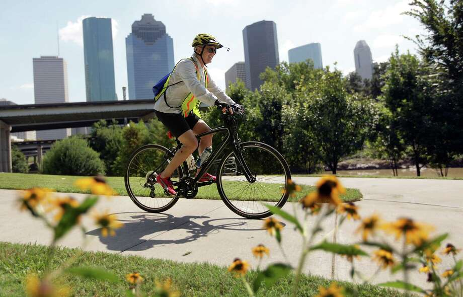 Peggy Moore rides her bike along the Sabine-To-Bagby Promenade on the Buffalo Bayou on Wednesday, Oct. 3, 2012, in Houston. The American Planning Association appointed The Buffalo Bayou as one of the 10 Great Public Spaces for 2012, under the organization's Great Places in America program. Photo: Mayra Beltran, Houston Chronicle / © 2012 Houston Chronicle