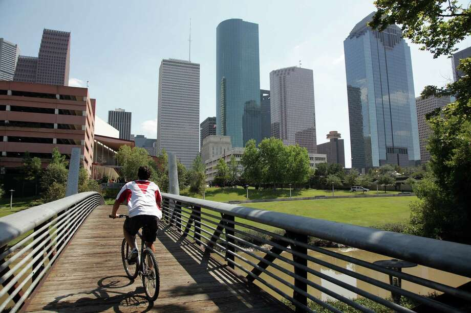 A cyclist rides over the Buffalo Bayou while exercising along the  Sabine-To-Bagby Promenade on Wednesday, Oct. 3, 2012, in Houston. Photo: Mayra Beltran, Houston Chronicle / © 2012 Houston Chronicle