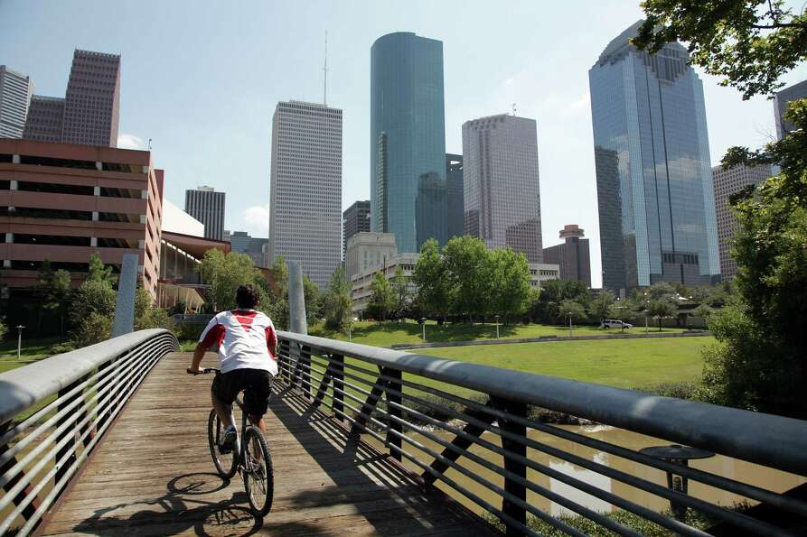 A cyclist rides over the Buffalo Bayou while exercising along the  Sabine-To-Bagby Promenade on Wedn