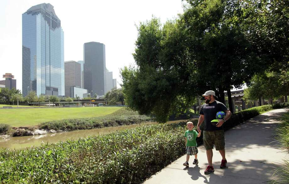 Jeremy Horton and his son Maddox Horton, 3, overlook the Buffalo Bayou  along the Sabine-To-Bagby Promenade on Wednesday, Oct. 3, 2012, in Houston. Photo: Mayra Beltran, Houston Chronicle / © 2012 Houston Chronicle