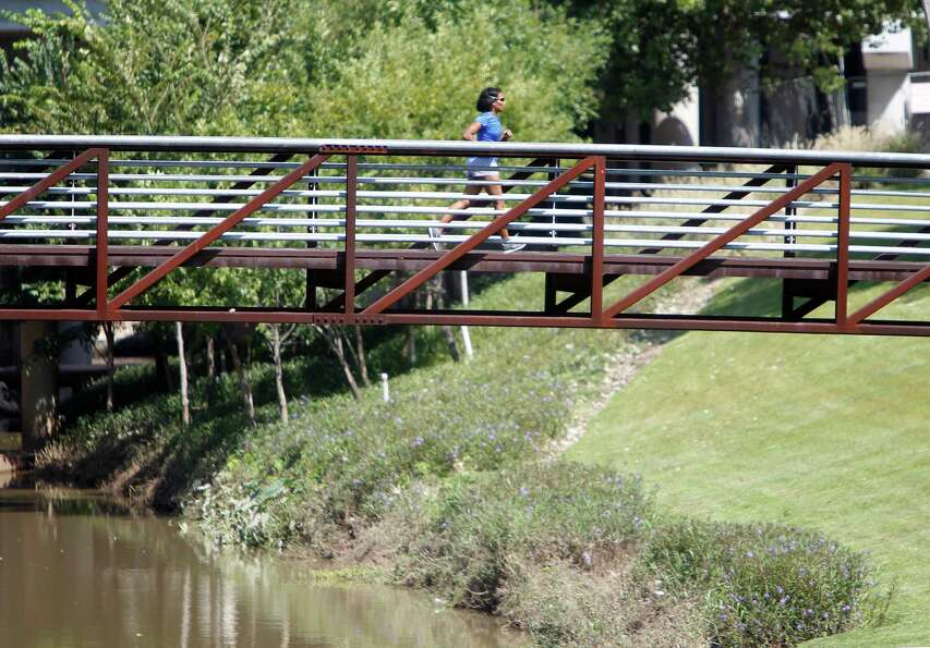 A runner crosses over the Buffalo Bayou.