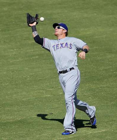 Josh Hamilton of the Texas Rangers, drops a fly ball hit by Yoenis Cespedes in centerfield that allowed Stephen Drew and Coco Crisp to score in the fourth inning on the error. The Oakland Athletics won the American League West division after they defeated the Texas Rangers at O.co Coliseum in Oakland, Calif., on Wednesday, October 3, 2012. Photo: Carlos Avila Gonzalez, The Chronicle