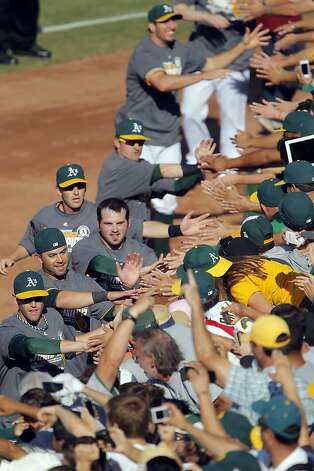A's players high five fans in the stands after the A's defeated the Texas Rangers. The Oakland Athletics won the American League West division after they defeated the Texas Rangers at O.co Coliseum in Oakland, Calif., on Wednesday, October 3, 2012. Photo: Carlos Avila Gonzalez, The Chronicle