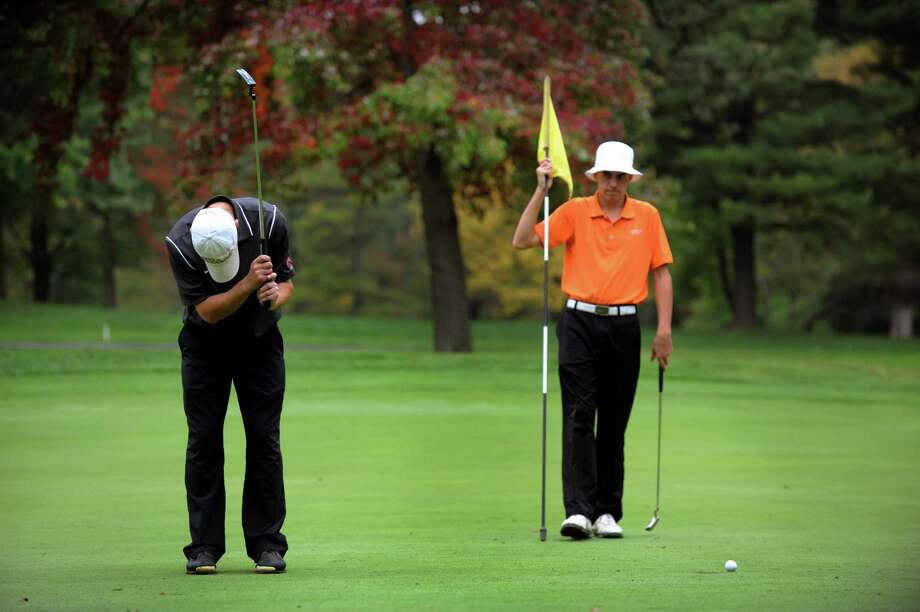 Niskayuna's Aaron Simone, left, reacts to a missed putt as Bethlehem's Jeff Palmerino tends the pin during the Section II Class A golf championship on Wednesday, Oct. 3, 2012, at Town of Colonie Golf Course in Colonie, N.Y. (Cindy Schultz / Times Union) Photo: Cindy Schultz / 00019228A