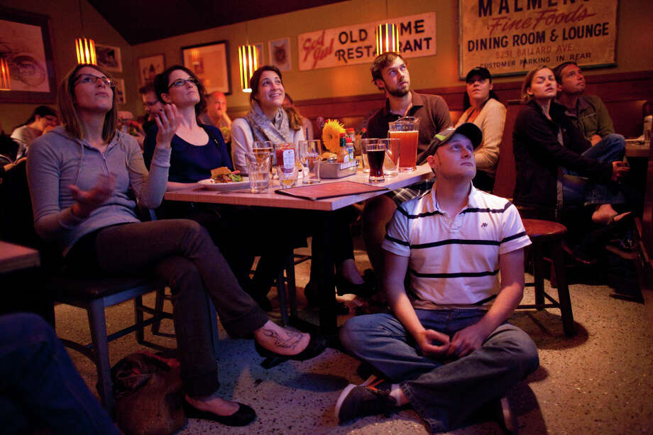 Chris Martin, bottom right, watches the screen during a debate watching party on Wednesday, October 3, 2012 at Hattie's Hat bar in Ballard. The neighborhood bar hosted a watching party, filling a back room with people watching the event. Photo: JOSHUA TRUJILLO / SEATTLEPI.COM