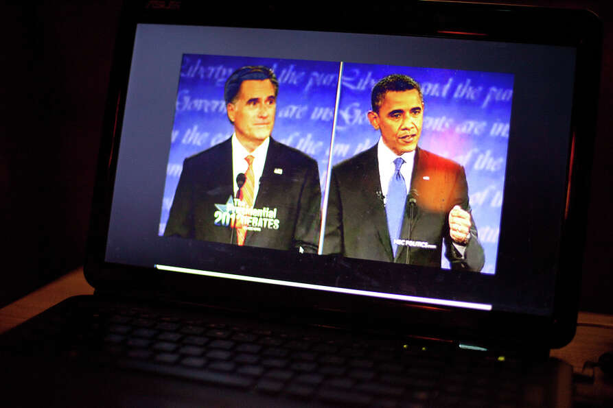 A screen shows the candidates during a debate watching party on Wednesday, October 3, 2012 at Hattie