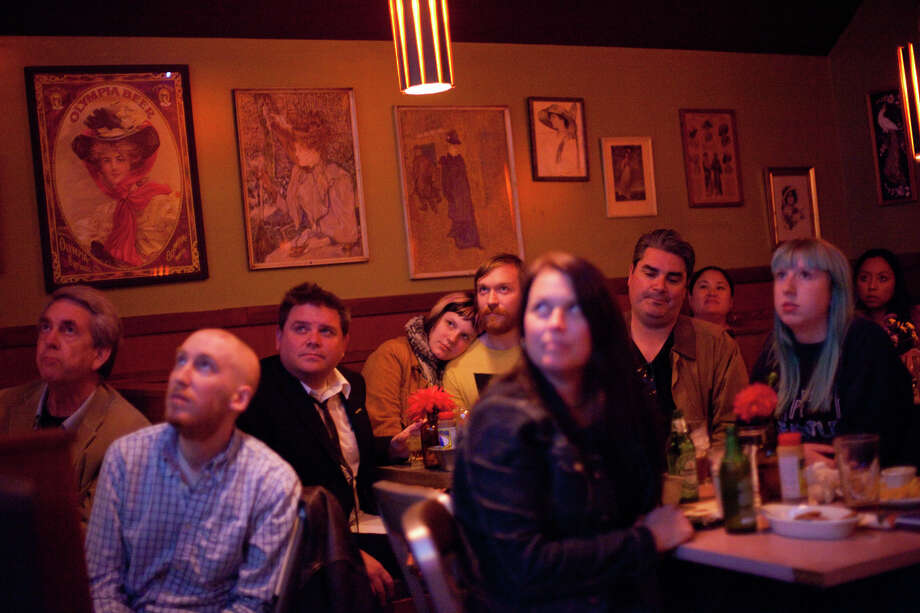 People watch the screen during a debate watching party on Wednesday, October 3, 2012 at Hattie's Hat bar in Ballard. The neighborhood bar hosted a watching party, filling a back room with people watching the event. Photo: JOSHUA TRUJILLO / SEATTLEPI.COM