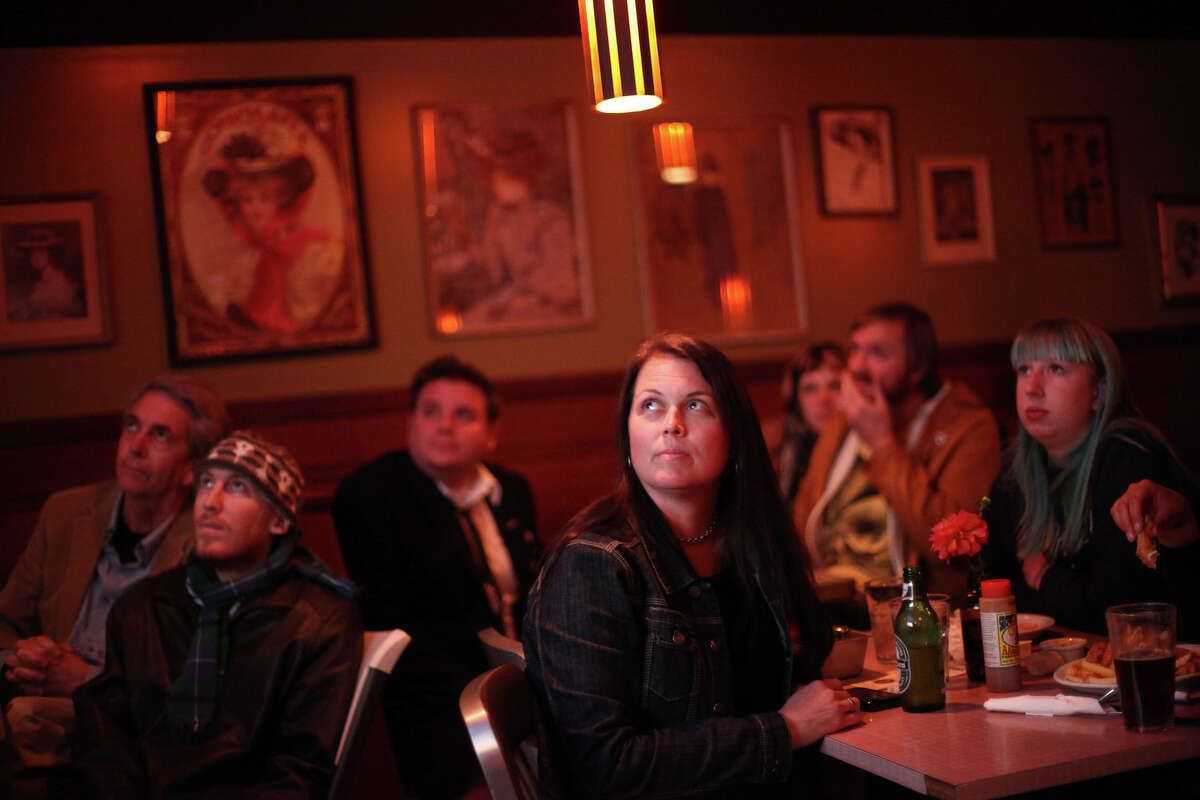 Leigh Anne Hagar, center, watches the screen during a presidential debate watching party on Wednesday, October 3, 2012 at Hattie's Hat bar in Ballard. The neighborhood bar hosted a watching party, filling a back room with people watching the event.