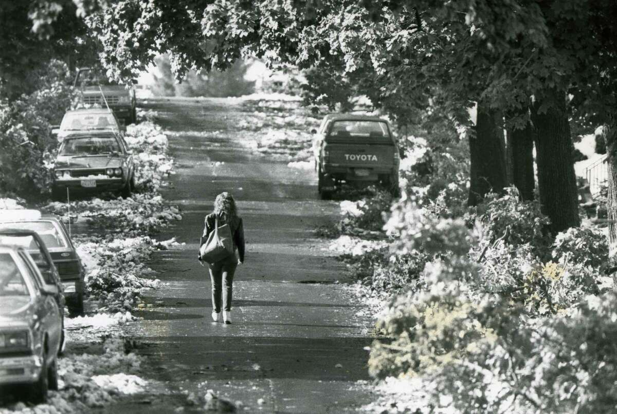 A young woman walks down an unusually heavy tree lined Pinewood Street, on October 5, 1987, as a result of the storm in Albany, N.Y. (Times Union / Skip Dickstein archive)