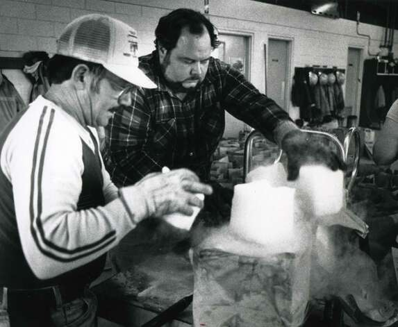 Dry ice was made available to residents in West Sand Lake, N.Y., Oct. 6, 1987, following widespread damage caused by a freak Autumn snowstorm on Oct. 4. Fran DeFilippis, left, and Michael Hicks, right, divide a 60 lb block of dry ice. (Paul D. Kniskern Sr. / Times Union archive)