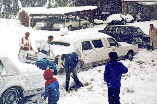 "Phil Hanby, left, and his cousin Jim Bonesteel, center, stand in their tuxedoes, by limousines on Phil's wedding day, as Phil's nephews help dig out from ""Fall's Snowy Crippler,"" a freak early snowstorm that caused power outages and fallen trees on October 4, 1987 in Wynantskill, NY. Only about half of the guests made it to the wedding of Phil and Marie in nearby Troy. They celebrate their 25th wedding anniversary on October 4, 2012. (Provided courtesy of the Hanby Family to the Times Union) Photo: Photograph Courtesy Of The Hanby / 00019517A"