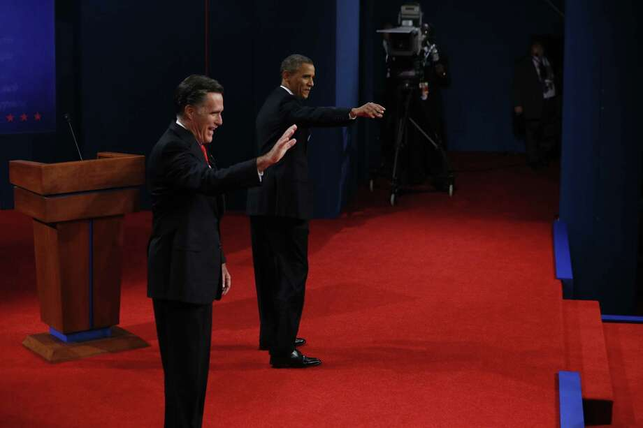 Republican presidential candidate Mitt Romney (L) and US President Barack Obama (R) arrive on the Magness Arena stage for their first debate at the University of Denver in Denver, Colorado, October 3, 2012. After hundreds of campaign stops, $500 million in mostly negative ads and countless tit-for-tat attacks,  Obama and Romney went head-to-head in their debut debate.    AFP PHOTO / Pool / Rick WILKINGRICK WILKING/AFP/GettyImages Photo: RICK WILKING, AFP/Getty Images / AFP