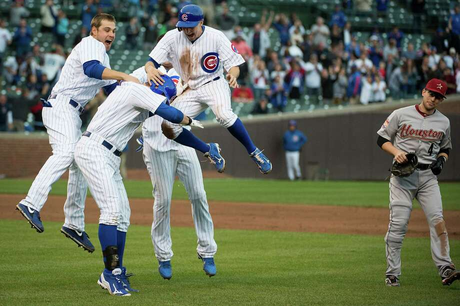 The Cubs' Bryan LaHair joins a melee with Brett Jackson, Tony Campana and Starlin Castro after his ninth-inning single beat Jed Lowrie, left, and the Astros 5-4. Photo: Smiley N. Pool / © 2012  Smiley N. Pool