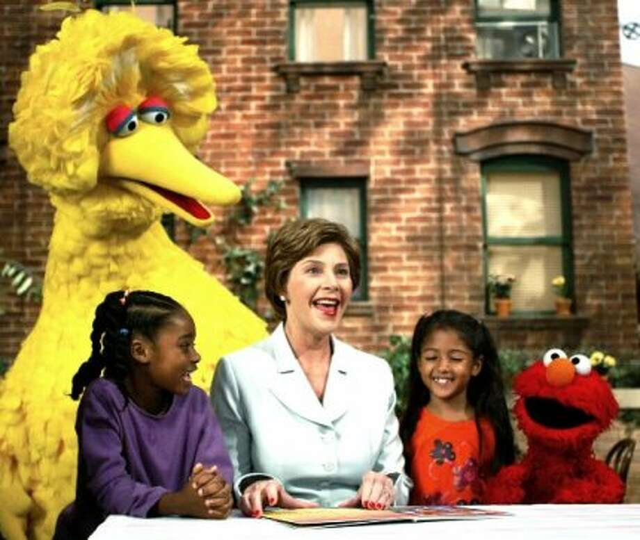 In 2002, Former First Lady Laura Bush, center, read a book to Sydney Martinez, Big Bird, Sienna Jerries and Elmo. (AP Photo)