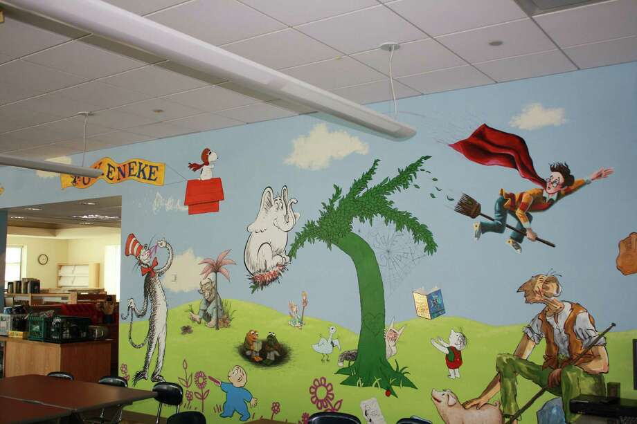 The mural in the Tokeneke library, which was donated by last year's fifth graderes, features prominent literary figures such as the Cat in the Hat and The Giving Tree. Photo: File Photo