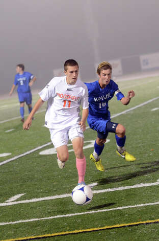 Ridgefield's Samuel Isaac (11) and Darien's Ben Highton (10) go after the ball during the boys soccer game at Ridgefield High School on Wednesday, Oct. 3, 2012. Photo: Amy Mortensen / Connecticut Post Freelance