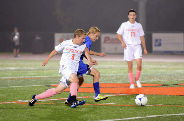 Darien's Spencer McMullin (11) controls the ball as Ridgefield's Travis Leiter (3) defends during the boys soccer game at Ridgefield High School on Wednesday, Oct. 3, 2012. Photo: Amy Mortensen / Connecticut Post Freelance
