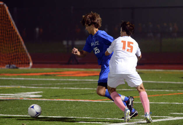 Darien's Alexei Gunya (25) gets the ball away from Ridgefield's Alexander Northcutt (15) during the boys soccer game at Ridgefield High School on Wednesday, Oct. 3, 2012. Photo: Amy Mortensen / Connecticut Post Freelance