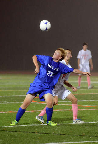 Darien's Henrik Stockinger (23) heads the ball as Ridgefield's Matthew Wilson (14) defends during the boys soccer game at Ridgefield High School on Wednesday, Oct. 3, 2012. Photo: Amy Mortensen / Connecticut Post Freelance