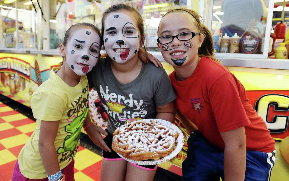 Kiele Barron, 8, Karlee Barron, 10, and Jillian Stewart, 12, of Winnie enjoy the festivities at the  43rd annual Rice Festival which kicked off on Wednesday, October, 3, 2012 at the Winnie-Stoell Park.  Photo taken: Randy Edwards/The Enterprise