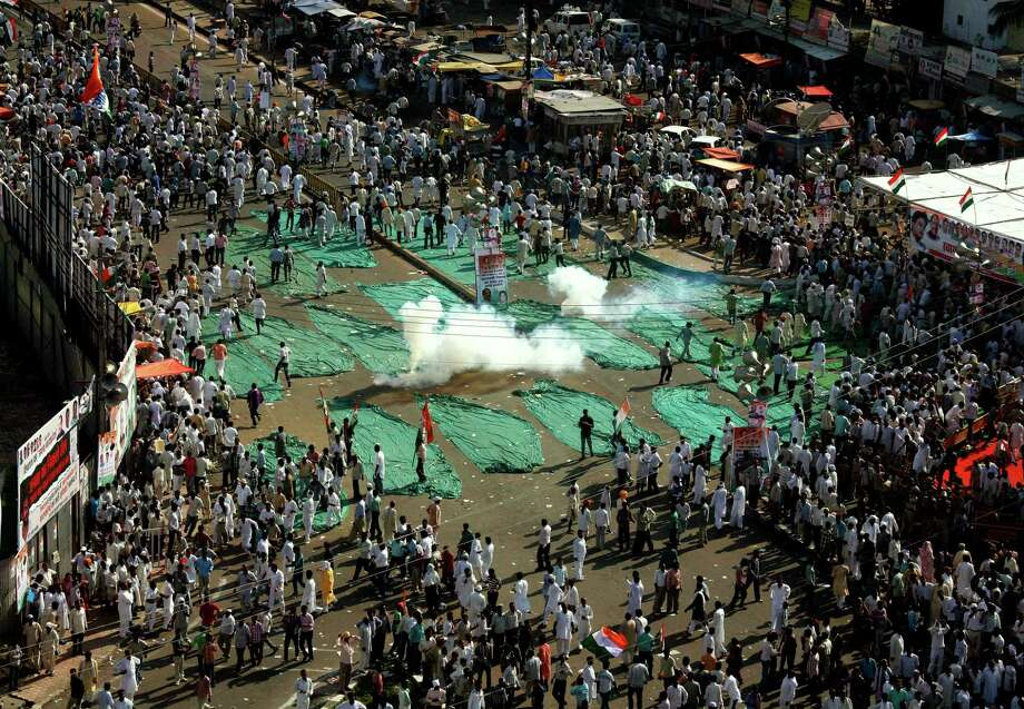 Indian policemen use tear gas shells  to disperse Congress party workers who marched to Madhya Pradesh state Chief Minister Shivraj Singh Chouhan's residence to protest against alleged corruption and the deteriorating law and lack of order in the state, in Bhopal, India, Thursday, Oct. 4, 2012. (AP Photo/Rajeev Gupta) Photo: Rajeev Gupta, Associated Press / AP