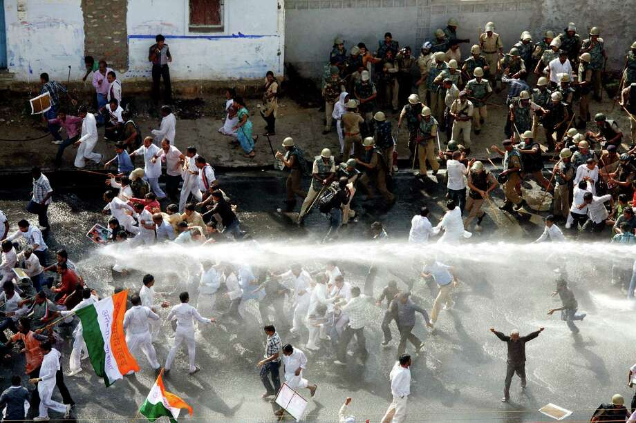 Indian policemen use batons and a water cannon to disperse Congress party workers who marched to Madhya Pradesh state Chief Minister Shivraj Singh Chouhan's residence to protest against alleged corruption and the deteriorating law and lack of order in the state, in Bhopal, India, Thursday, Oct. 4, 2012. (AP Photo/Rajeev Gupta) Photo: Rajeev Gupta, Associated Press / AP
