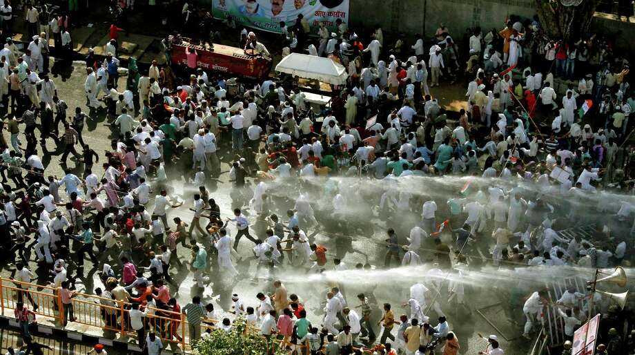 Indian policemen use a water cannon to disperse Congress party workers who marched to Madhya Pradesh state Chief Minister Shivraj Singh Chouhan's residence to protest against alleged corruption and the deteriorating law and lack of order in the state, in Bhopal, India, Thursday, Oct. 4, 2012. (AP Photo/Rajeev Gupta) Photo: Rajeev Gupta, Associated Press / AP