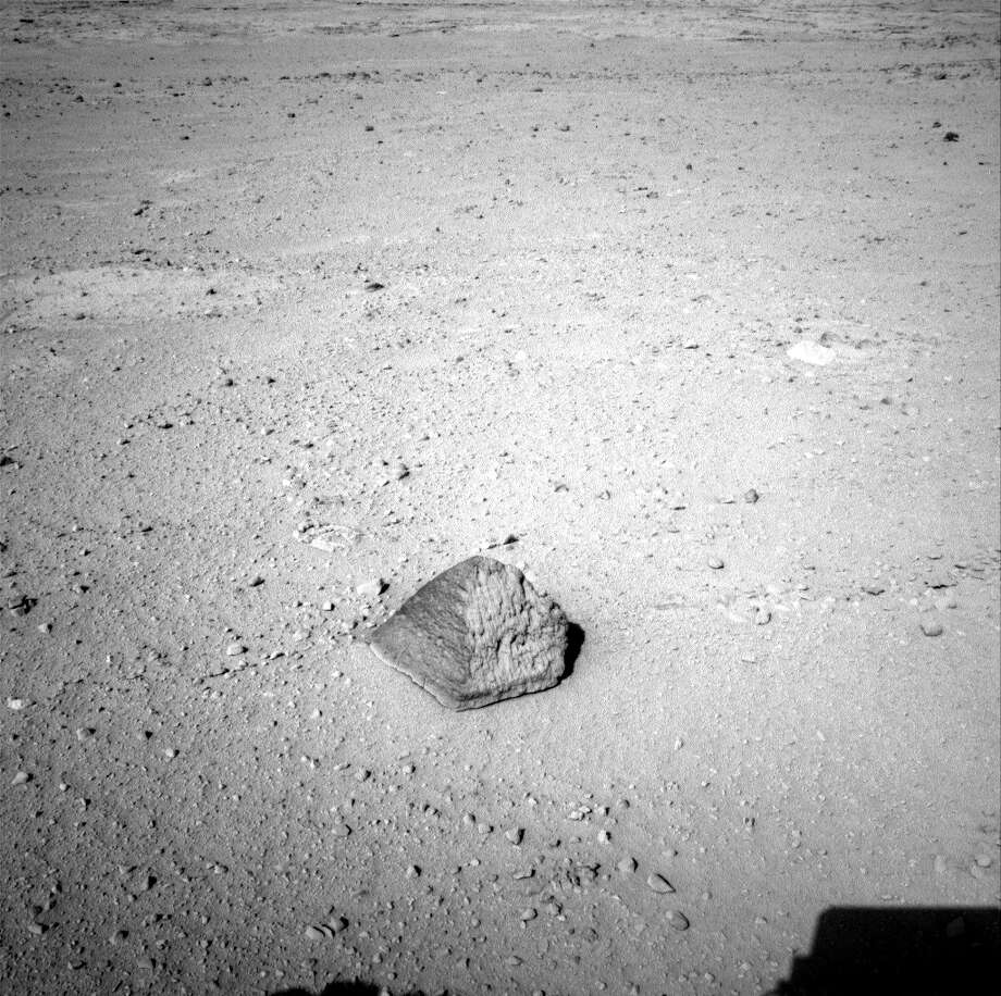 "This Sept. 19, 2012 photo provided by NASA shows a rock about 8 feet (2.5 meters) in front of the Curiosity rover on Mars. The rock is about 10 inches (25 centimeters) tall and 16 inches (40 centimeters) wide. The team has assessed it as a suitable target for the first use of Curiosity's contact instruments on a rock, and named it after the late Jacob Matijevic, who was the surface operations systems chief engineer for the Mars Science Laboratory Project and the project's Curiosity rover. (AP Photo/NASA/JPL-Caltech) The rock has been named ""Jake Matijevic."" This commemorates Jacob Matijevic (1947-2012), who was the surface operations systems chief engineer for the Mars Science Laboratory Project and the project's Curiosity rover. He was also a leading engineer for all of the previous NASA Mars rovers: Sojourner, Spirit and Opportunity. Curiosity's contact instruments are on a turret at the end of the rover's arm. They are the Alpha Particle X-Ray Spectrometer for reading a target's elemental composition and the Mars Hand Lens Imager for close-up imaging. Photo: Associated Press / NASA/JPL-Caltech"
