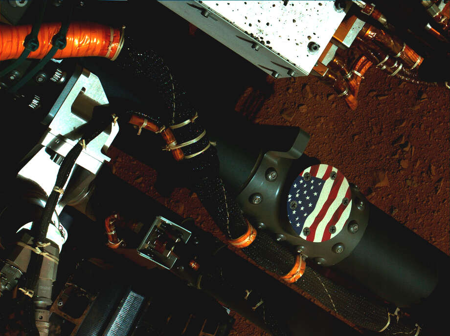"This Sept. 19, 2012 image provided by NASA shows a view of the United States flag medallion on NASA's Mars rover Curiosity that was taken by the rover's Mars Hand Lens Imager (MAHLI). The flag is one of four ""mobility logos"" placed on the rover's mobility rocker arms. The circular medallion of the flag is made of anodized aluminum and measures 2.68 inches (68 millimeters) in diameter. The medallion was affixed with bolts to locations on the rocker arms where flight hardware was once considered, but ultimately deemed unnecessary. (AP Photo/NASA) Photo: Courtesy Photo, NASA / NASA"