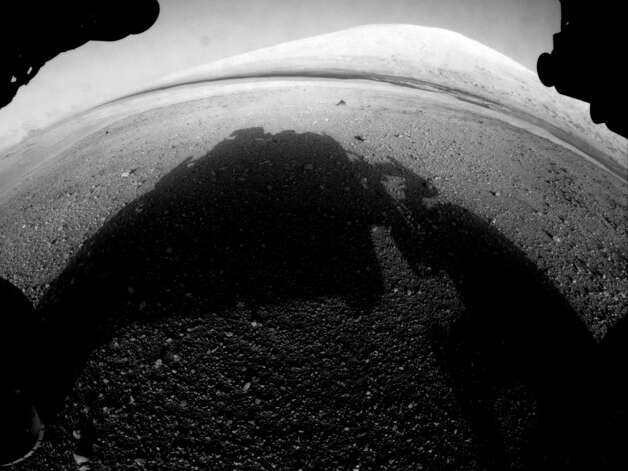 This image taken by NASA's Curiosity shows what lies ahead for the rover -- its main science target, informally called Mount Sharp, Monday, Aug. 6, 2012. The rover's shadow can be seen in the foreground, and the dark bands beyond are dunes. Rising up in the distance is the highest peak of Mount Sharp at a height of about 3.4 miles (5.5 kilometers), taller than Mt. Whitney in California. The Curiosity team hopes to drive the rover to the mountain to investigate its lower layers, which scientists think hold clues to past environmental change. This image was captured by the rover's front left Hazard-Avoidance camera at full resolution shortly after it landed. It has not yet been linearized to remove the distorted appearance that results from its fisheye lens. (AP Photo/NASA/JPL-Caltech) Photo: MSL Curiosity, Associated Press / AP