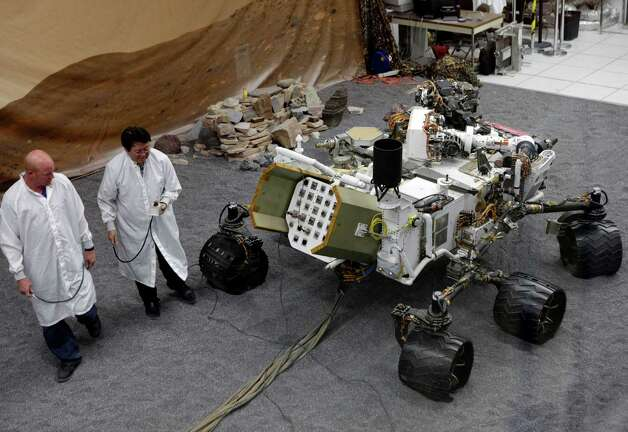 Engineers work on a model of the Mars rover Curiosity at the Spacecraft Assembly Facility at NASA's Jet Propulsion Laboratory in Pasadena, Calif., Thursday, Aug. 2, 2012. After traveling 8 1/2 months and 352 million miles, Curiosity will attempt a landing on Mars the night of Aug. 5, 2012. (AP Photo/Damian Dovarganes) Photo: Damian Dovarganes, Associated Press / AP