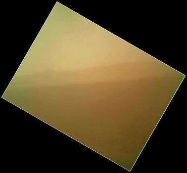 This image released on Tuesday Aug. 7,2012 by NASA shows the first color view of the north wall and rim of Gale Crater where NASA's rover Curiosity landed Sunday night. The picture was taken by the rover's camera at the end of its stowed robotic arm and appears fuzzy because of dust on the camera's cover. (AP Photo/NASA) Photo: HOPD, Associated Press / NASA