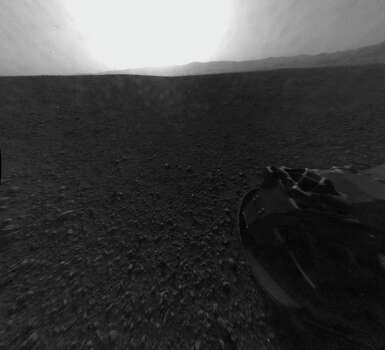 "This photo provided by NASA shows a full-resolution version of one of the first images taken by a rear Hazard-Avoidance camera on NASA's Curiosity rover, which landed on Mars the Sunday evening, Aug. 5, 2012. The image was originally taken through a ""fisheye"" wide-angle lens, but has been ""linearized"" so that the horizon looks flat rather than curved. A Hazard-avoidance camera on the rear-left side of Curiosity obtained this image. Part of the rim of Gale Crater, which is a feature the size of Connecticut and Rhode Island combined, stretches from the top middle to the top right of the image. One of the rover's wheels can be seen at bottom right. (AP Photo/NASA/JPL-Caltech) Photo: MSL Curiosity, Associated Press / NASA"
