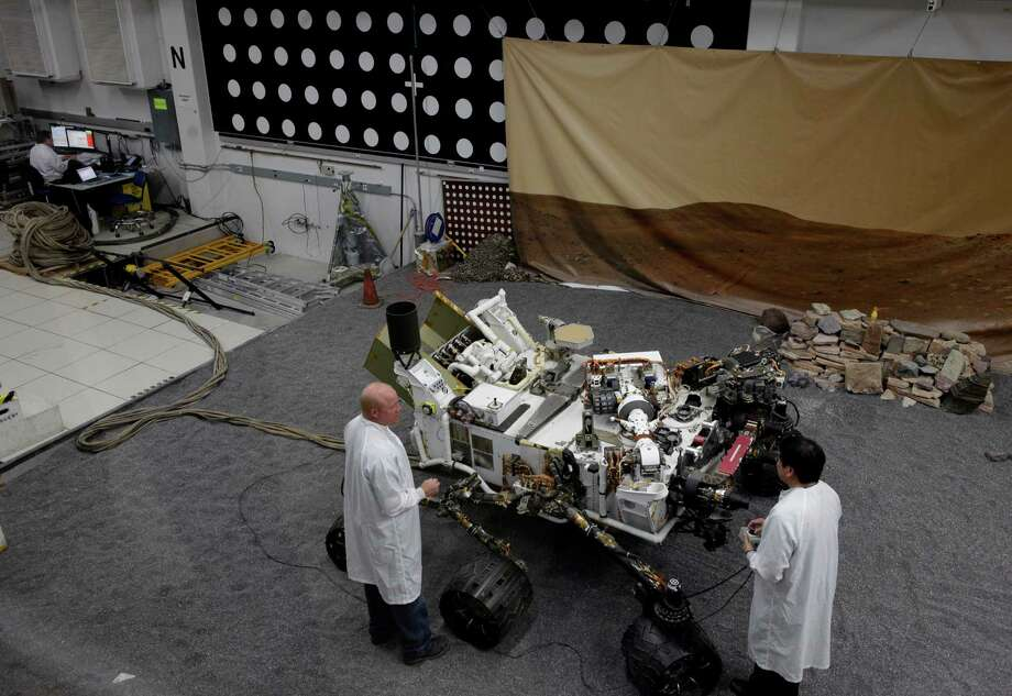 FILE- In this file photo taken Thursday, Aug. 2, 2012, engineers work on a model of the Mars rover Curiosity at the Spacecraft Assembly Facility at NASA's Jet Propulsion Laboratory in Pasadena, Calif., After traveling 8 1/2 months and 352 million miles, Curiosity will attempt a landing on Mars the night of Aug. 5, 2012. (AP Photo/Damian Dovarganes, File) Photo: Damian Dovarganes, Associated Press / AP