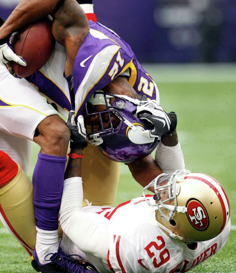 Minnesota Vikings wide receiver Percy Harvin, top, is tackled by San Francisco 49ers defensive back Chris Culliver after making a reception during the first half of an NFL football game on Sunday, Sept. 23, 2012, in Minneapolis. Photo: Genevieve Ross, Associated Press / FR170496 AP