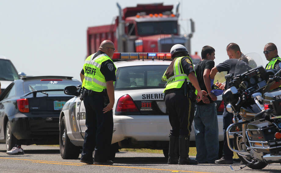 Officers from the Bexar County Sheriff's Office detain a suspect (in handcuffs) on the feeder road of Interstate 37 South near Donop road and Braunig Lake on October 4, 2012. Bexar County sheriff's Lt. Jose Trevino said the department received a call about shots fired from a black car along the access road of Interstate 37 near Donop Road about 1 p.m. Trevino said it appears as though two men inside the vehicle opened fire on a silver car along the access road that also was occupied by two men. Nobody was injured during the incident. Photo: John Davenport/Express-News