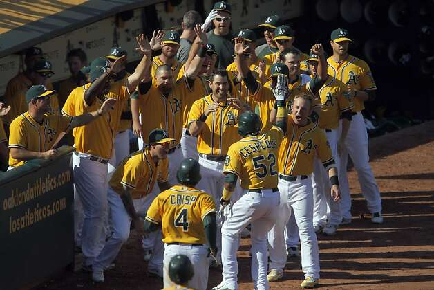 The rout was on when Yoenis Céspedes, Coco Crisp and Stephen Drew scored on Brandon Moss' eighth-inning single to right (and Nelson Cruz's error) Wednesday. The dugout emptied to greet the run-scorers, a precursor to the wild celebration that erupted when the division was won an inning later. Photo: Carlos Avila Gonzalez, The Chronicle