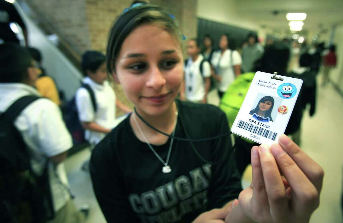 Tira Starr, an 8th grader at Anson Jones Middle School, shows her ID badge as students change classes. Students at the school are using new identification badges that have a built in chip that enables school attendance workers to see where a student is while on campus. Oct. 1, 2012.