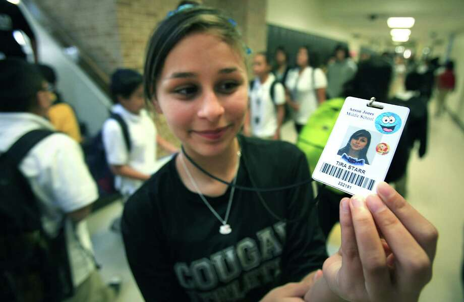Tira Starr, an 8th grader at Anson Jones Middle School, shows her ID badge as students change classes. Students at the school are using new identification badges that have a built in chip that enables school attendance workers to see where a student is while on campus.  Oct. 1, 2012. Photo: BOB OWEN, San Antonio Express-News / © 2012 San Antonio Express-News