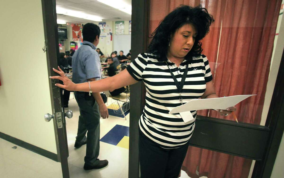 Felicia Canales, checks her list of absent students whose ID card showed up after a computer search, as she leaves a classroom. Students at Anson Jones Middle School are using new identification badges that have a built in chip that enables school attendance workers to see where a student is while on campus. Oct. 1, 2012.